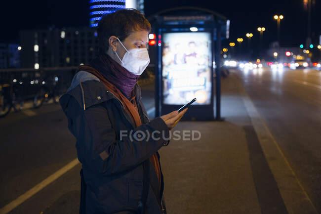 Женщина в маске с мобильного телефона, стоящая на автобусной остановке в городе — стоковое фото