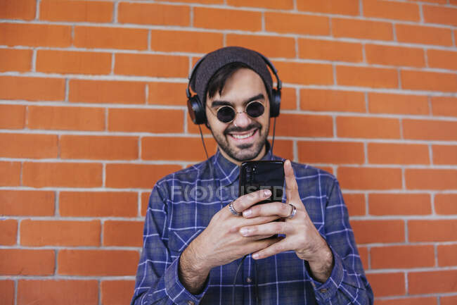 Smiling young man listening music while using smart phone against brick wall — Stock Photo