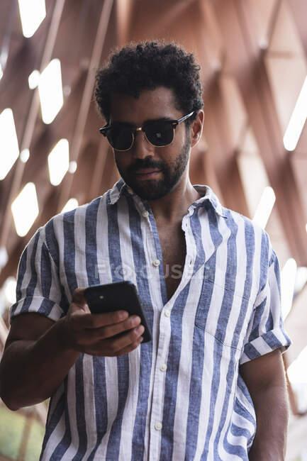Uomo che utilizza il telefono cellulare mentre in piedi in città — Foto stock
