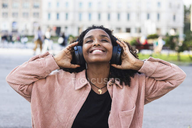 Улыбающиеся молодые с закрытыми глазами слушают музыку через наушники в городе — стоковое фото