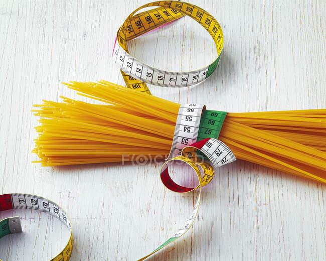 Esparguete cru envolto com fita métrica — Fotografia de Stock