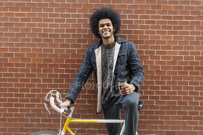 Joven sosteniendo café mientras está de pie con bicicleta contra la pared de ladrillo - foto de stock