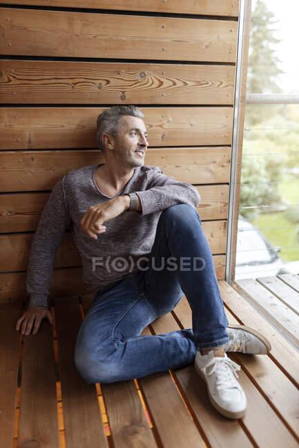Усміхнений чоловік дивиться у вікно, сидячи вдома на підлозі. — стокове фото