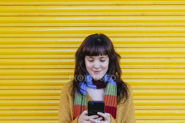 Smiling woman text messaging on smart phone while standing against shutter — Stock Photo