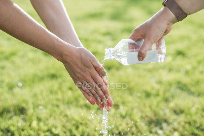 Woman assisting friend in washing hands from water at park on sunny day — Stock Photo