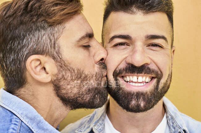 Гей цілує усміхненого чоловіка стоячи проти жовтої стіни. — стокове фото