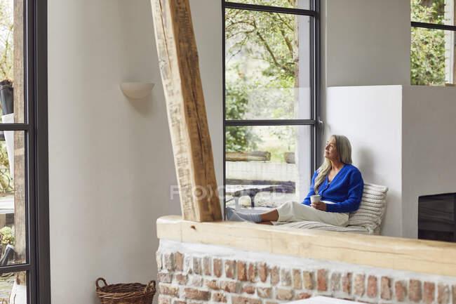 Mulher madura pensativo com xícara de café olhando através da janela em casa — Fotografia de Stock
