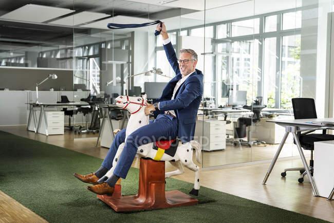 Brincalhão masculino profissional fingindo montar cavalo de balanço no escritório — Fotografia de Stock