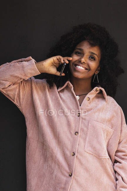 Smiling young woman on phone call against black wall — Stock Photo