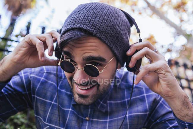 Sorridente giovane uomo in occhiali da sole con le cuffie nel parco pubico — Foto stock