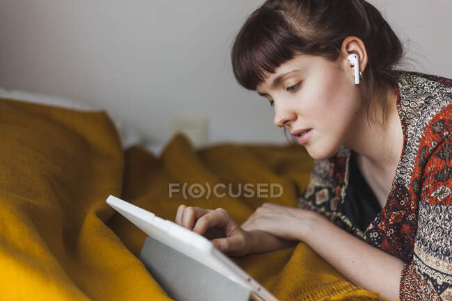 Молода жінка дивиться онлайн - заняття через цифровий планшет з бездротовими навушниками, лежачи на ліжку. — стокове фото