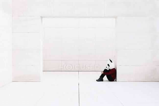 Mujer deprimida con máscara de panda sentada en la puerta contra la pared blanca - foto de stock