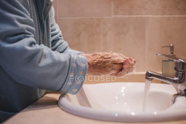 Mujer mayor lavándose las manos por fregadero en casa - foto de stock