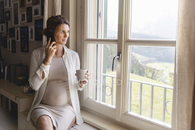 Беременная женщина разговаривает по мобильному телефону, глядя в окно — стоковое фото
