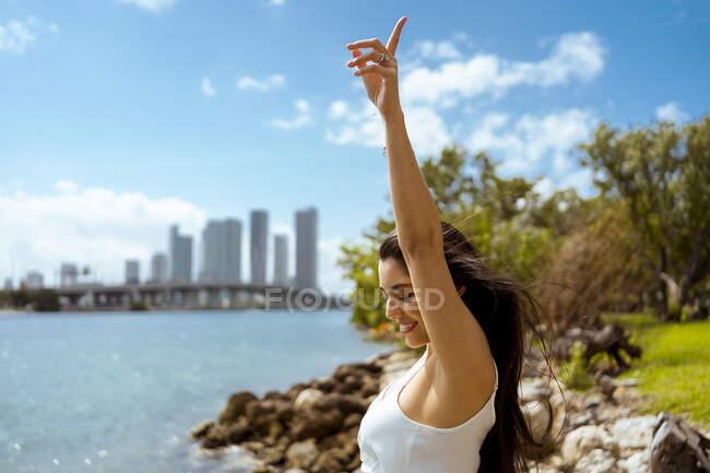 Felice giovane turista femminile godendo mentre ballava con la mano sollevata nella giornata di sole — Foto stock