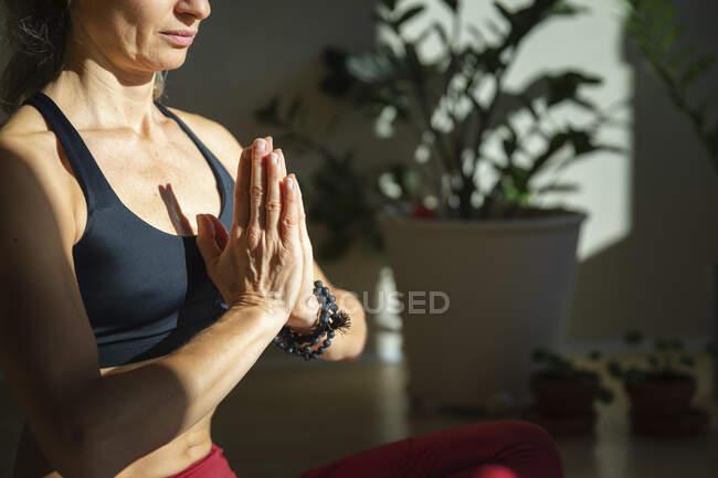 Зрелая женщина медитирует, сжимая руки дома в солнечный день. — стоковое фото