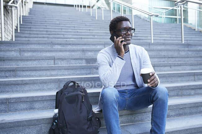 Hombre de negocios respondiendo a la llamada telefónica mientras sostiene la taza de café desechable en la escalera — Stock Photo