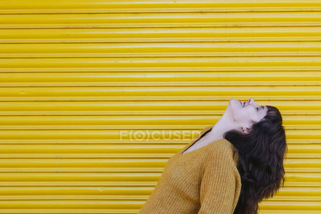 Молода жінка сміється, стоячи біля затвора. — стокове фото