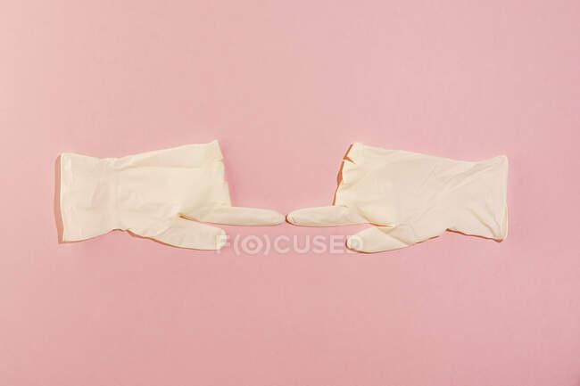 Студія з парою хірургічних рукавиць торкається вказівними пальцями. — стокове фото