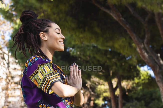 Улыбающаяся красивая молодая женщина медитирует, сжимая руки, практикуя йогу в парке — стоковое фото