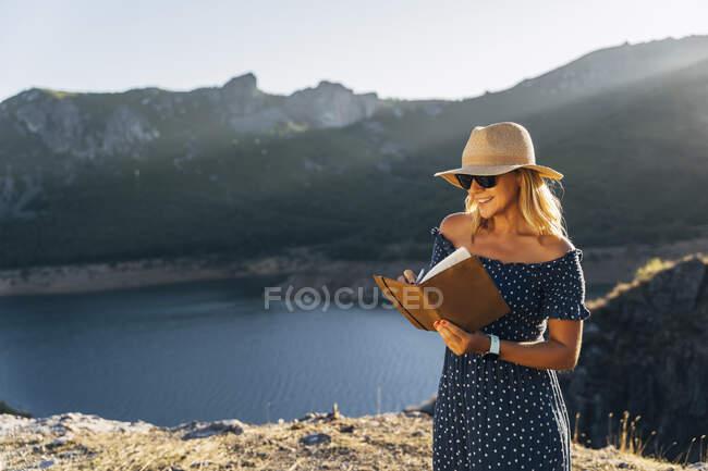 Donna sorridente in cappello scrivere in diario contro lago nella giornata di sole durante le vacanze — Foto stock