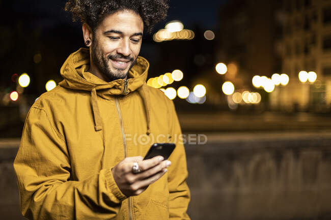 Man wearing hooded shirt using mobile phone while standing outdoors — Stock Photo