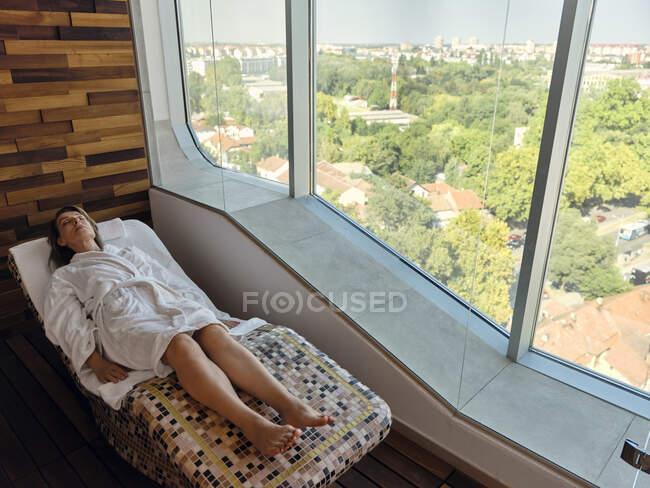 Vista de ángulo alto de la mujer mayor que se relaja mientras está tumbada en la silla de salón en el spa - foto de stock