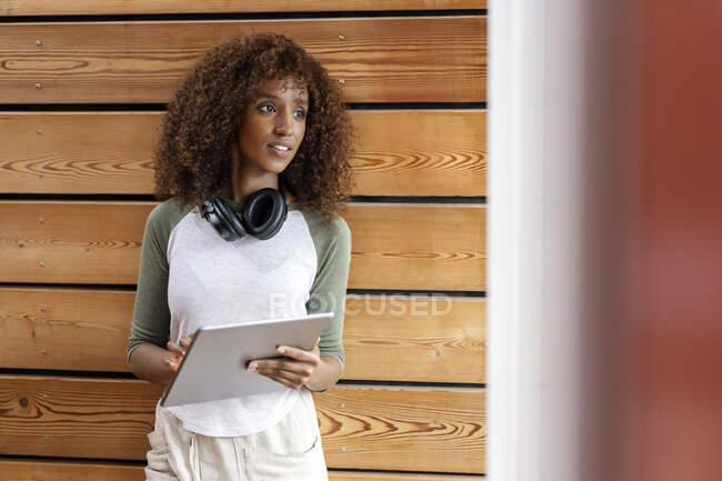 Donna con tablet digitale guardando lontano mentre in piedi a casa — Foto stock