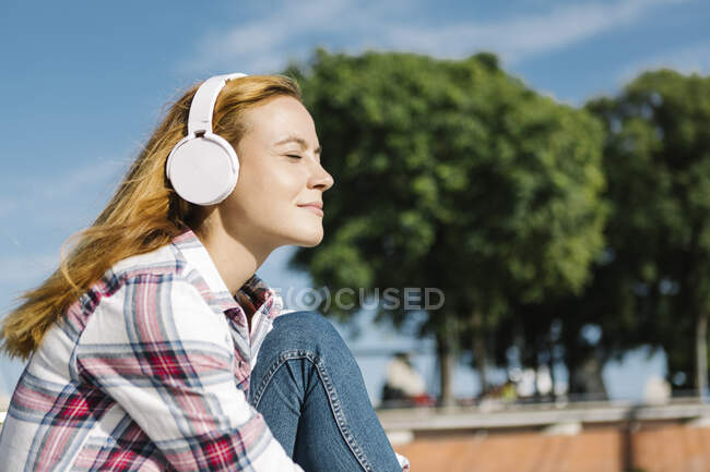 Woman with eyes closed listening music through headphone on sunny day — Stock Photo