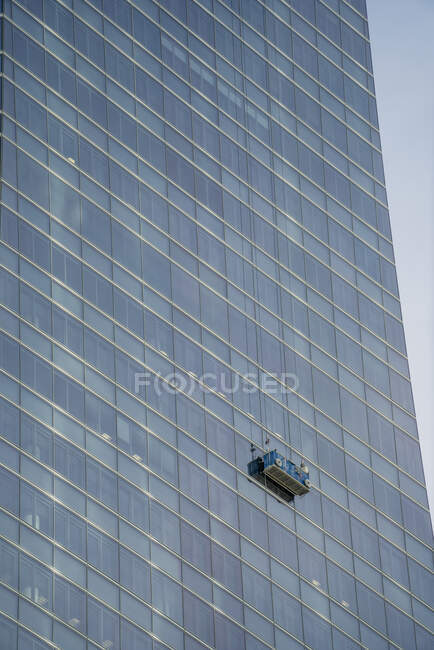 Spain, Madrid, Window cleaners platform hanging in front ofskyscraper windows — Stock Photo