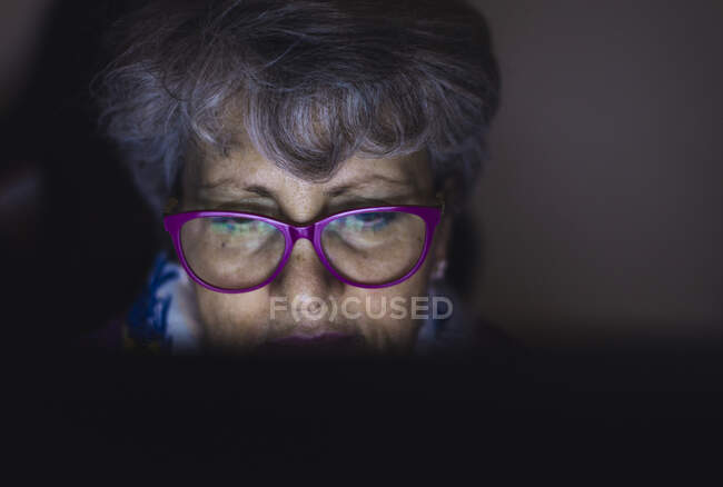 Close-up of teacher with gray hair working over laptop at home — Stock Photo