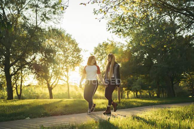 Joven pareja lesbiana cogida de la mano mientras camina por el sendero - foto de stock