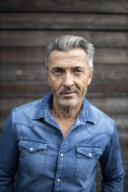 Уверенный человек, стоящий у деревянной стены — стоковое фото