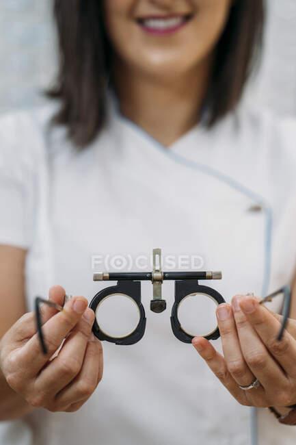 Усміхаючись, жінка - оптик з окулярами у клініці. — стокове фото