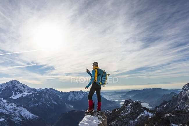 Mature male hiker using smart phone while standing on top of mountain, Orobic alps, Lecco, Italy — Stock Photo