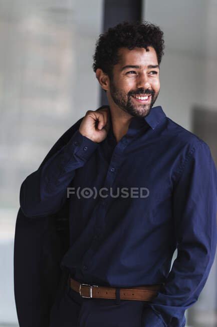 Hombre de negocios sonriente sosteniendo la chaqueta mientras está de pie en la ciudad - foto de stock