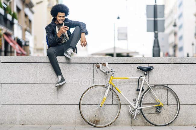 Молодий чоловік з кучерявим волоссям за допомогою смартфона сидячи на стіні. — стокове фото