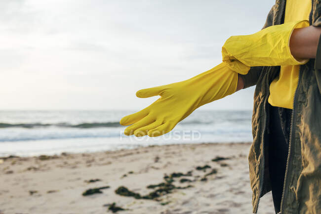 Woman standing and wearing protective glove for cleaning beach against sky — Stock Photo
