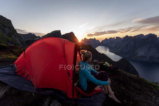 Donna ammirando vista mentre seduto in campo sulla montagna a Reinebringen. Lofoten, Norvegia — Foto stock