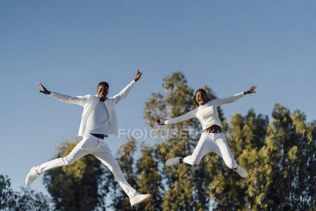 Alegre pareja heterosexual disfrutando del día mientras salta contra el cielo despejado a la luz del sol - foto de stock