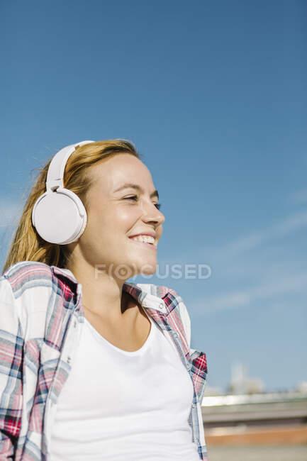 Счастливая женщина слушает музыку в наушниках, глядя на голубое небо в солнечный день — стоковое фото