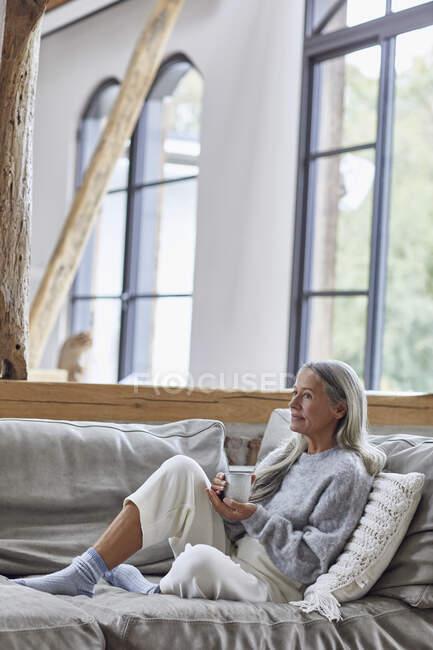 Задумчивая зрелая женщина смотрит в сторону, держа чашку кофе дома — стоковое фото