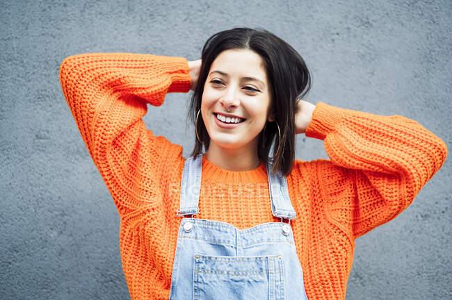 Mulher sorridente vestindo camisola laranja olhando para longe, enquanto em pé contra a parede cinza — Fotografia de Stock