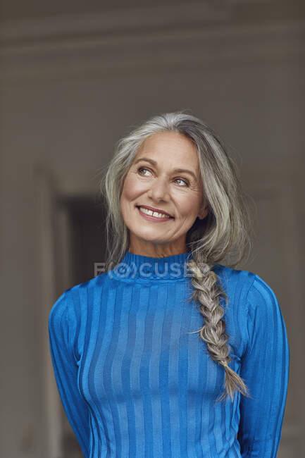Pensativa mujer madura sonriendo mientras mira hacia otro lado en casa - foto de stock