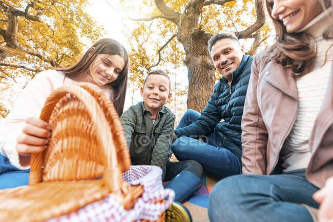 Улыбающиеся дети открывают корзину с едой, а осенью родители сидят на одеяле для пикника в парке — стоковое фото