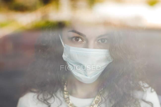 Hermosa mujer joven con mascarilla protectora vista a través de una ventana de vidrio durante la pandemia de COVID-19 - foto de stock