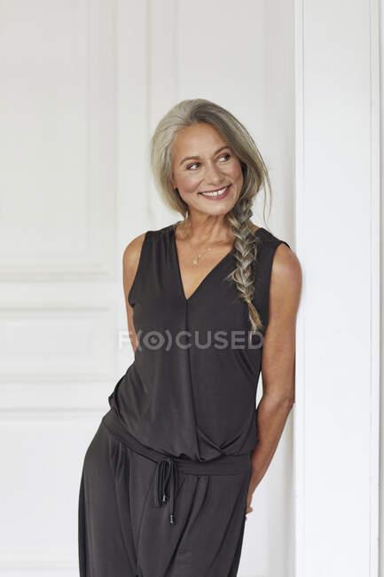 Усміхнена доросла жінка мріє, коли спирається на стіну вдома. — стокове фото