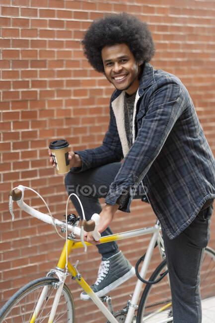 Sorridente giovane uomo in possesso di caffè mentre seduto sulla bicicletta contro muro di mattoni — Foto stock