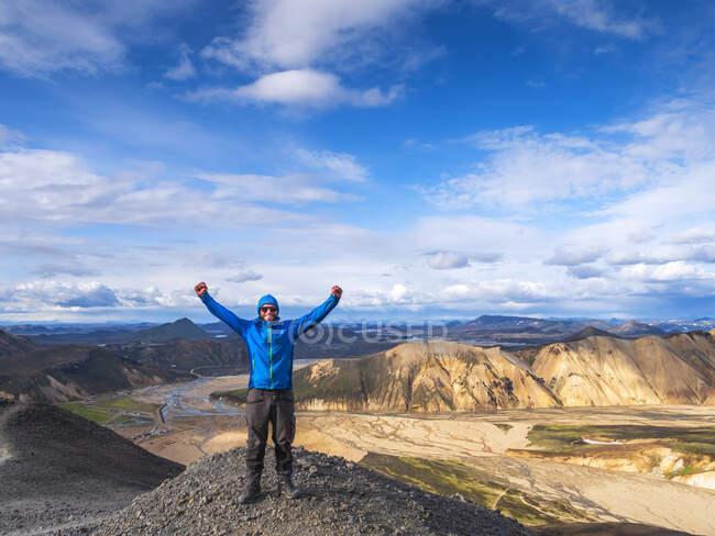 Hiker posing with raised arms on top of volcanic hill inLandmannalaugar — Stock Photo