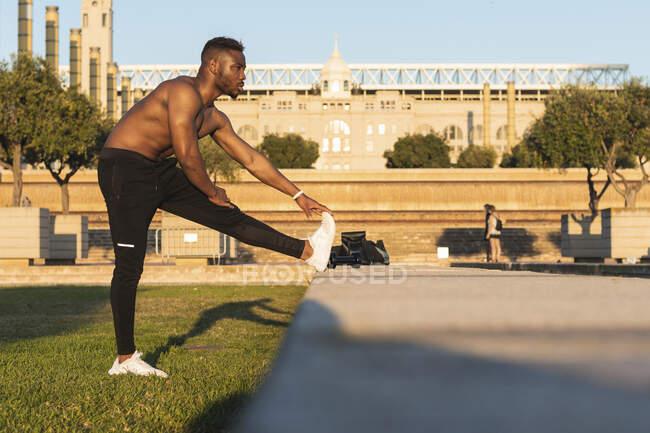 Спортсмен робить зігрівання вправ, розтягуючи ногу в парку. — стокове фото
